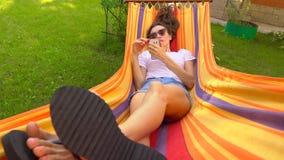 Красивая кавказская девушка брюнет отбрасывая в ярком гамаке и используя ее smartphone видео 4K сток-видео