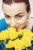 Красивая кавказская женщина представляя с букетом розы желтого цвета Стоковые Изображения RF