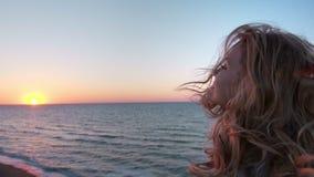Красивая кавказская курчавая белокурая молодая женщина на восходе солнца или заходе солнца океаном Ветер развивает волосы Она дыш сток-видео