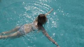 Красивая кавказская модель, молодая женщина плавает в бассейне с открытым морем в гостинице, под открытым небом против как крюка  видеоматериал