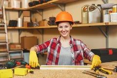 Красивая кавказская молодая женщина коричнев-волос работая в мастерской плотничества на месте таблицы Стоковое фото RF