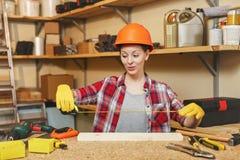 Красивая кавказская молодая женщина работая в мастерской плотничества на месте таблицы Стоковое Фото