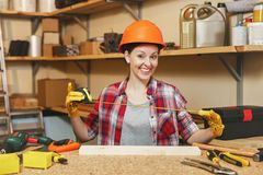 Красивая кавказская молодая женщина работая в мастерской плотничества на месте таблицы Стоковые Изображения