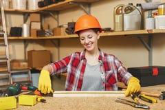 Красивая кавказская молодая женщина работая в мастерской плотничества на месте таблицы Стоковая Фотография