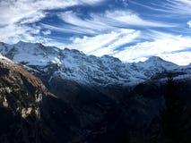 Красивая картина облака с голубым небом поверх каменной горы и белого снега покрыла стоковые изображения