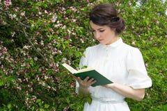 Красивая книга чтения женщины в зацветая саде весны Стоковые Фотографии RF