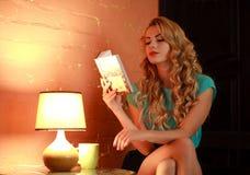 Красивая книга чтения женщины на таблице в уютном доме кафа Стоковое фото RF