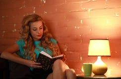 Красивая книга чтения женщины на таблице в уютном доме кафа Стоковая Фотография