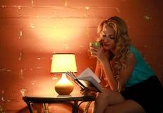 Красивая книга чтения женщины на таблице в уютном доме кафа Стоковые Изображения