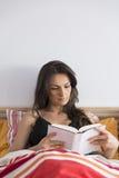 Красивая книга чтения женщины пока лежащ в кровати дома Стоковая Фотография