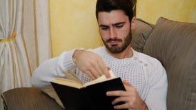 Красивая книга чтения молодого человека дома, усаживание на кресле видеоматериал
