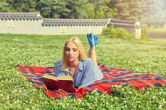 Красивая книга чтения студента молодой женщины на траве Стоковая Фотография