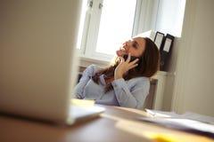 Красивая коммерсантка в домашнем офисе говоря на мобильном телефоне Стоковая Фотография RF