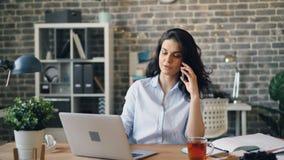 Красивая коммерсантка говоря на мобильном телефоне и печатая на ноутбуке в офисе акции видеоматериалы