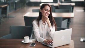 Красивая коммерсантка использует смартфон и ноутбук для работы в кафе, замедленном движении видеоматериал