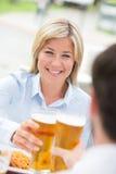 Красивая коммерсантка провозглашать стекло пива с мужским коллегой на ресторане Стоковые Изображения