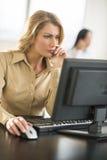 Красивая коммерсантка работая на компьютере на столе в офисе Стоковое Изображение