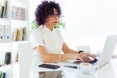 Красивая коммерсантка работая с ее компьтер-книжкой в офисе Стоковые Фото