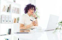 Красивая коммерсантка работая с ее компьтер-книжкой в офисе Стоковые Изображения