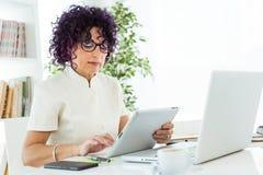 Красивая коммерсантка работая с ее цифровой таблеткой в офисе Стоковая Фотография RF
