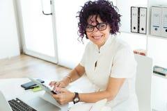 Красивая коммерсантка работая с ее цифровой таблеткой в офисе Стоковые Фото
