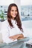 Красивая коммерсантка сидя на столе офиса Стоковые Фото