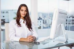 Красивая коммерсантка сидя на столе офиса Стоковые Фотографии RF