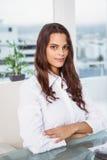 Красивая коммерсантка сидя на столе офиса Стоковая Фотография RF