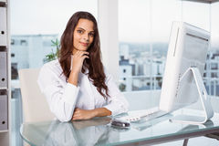 Красивая коммерсантка сидя на столе офиса Стоковое Фото