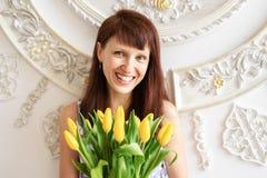Красивая коричнев-с волосами девушка с большим букетом желтых тюльпанов смеясь весело против белой стены с картиной стоковое изображение