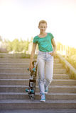 Красивая красивая девушка едет на шоссе на улице Longboard сценарной Солнечный тонизировать Портрет конца-вверх Стоковые Изображения RF