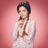 Красивая красная женщина волос в обмундировании зимы: теплые свитер, шарф и шляпа с снегом на всем она Изолированный на розовом к Стоковая Фотография RF