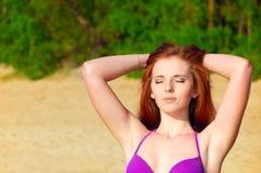 Красивая красная женщина волос представляя на пляже Стоковое Изображение RF