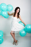 Красивая курчавая девушка в белом платье и солнечных очках в стиле диско играя с воздушными шарами Стоковое Изображение RF