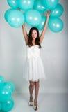 Красивая курчавая девушка в белом платье и солнечных очках в стиле диско играя с воздушными шарами Стоковая Фотография RF