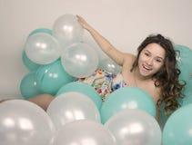 Красивая курчавая девушка в пестротканом платье играя с воздушными шарами Стоковые Фото