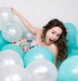 Красивая курчавая девушка в пестротканом платье играя с воздушными шарами Стоковое фото RF