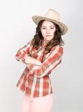 Красивая курчавая девушка в розовых брюках, рубашке шотландки и ковбойской шляпе Стоковые Фото