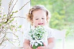 Красивая курчавая девушка малыша держа первую весну цветет Стоковое Изображение