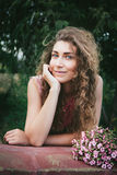 Красивая курчавая женщина с цветками в парке Стоковые Фотографии RF