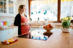 Красивая кухня ki беременной женщины стоковые фотографии rf