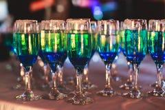 Красивая линия различных покрашенных коктеилей спирта с дымом на рождественской вечеринке, текила, Мартини, водочке, и других на  стоковые фото