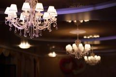 Красивая люстра при включении несколько ламп темный потолок стоковые изображения
