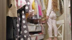 Красивая маленькая девочка выбирает платье в домашнем шкафе : видеоматериал