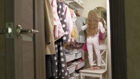 Красивая маленькая девочка выбирает платье в домашнем шкафе : сток-видео