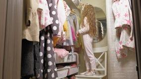 Красивая маленькая девочка выбирает платье в домашнем шкафе : акции видеоматериалы