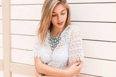 Красивая маленькая девочка в белой кружевной блузке смотря вниз с близко стоковое фото