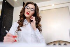 Красивая маленькая девочка в белой рубашке и стеклах говоря на мобильном телефоне Стоковое Изображение RF