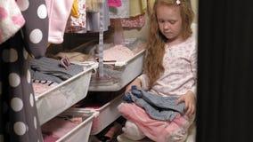Красивая маленькая девочка в домашнем шкафе Модные дети акции видеоматериалы