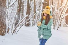 Красивая маленькая девочка в связанной шляпе, играя в снеге в лесе Стоковые Изображения RF